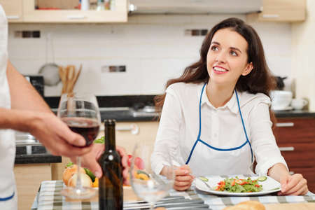 Beautiful young smiling woman eating salad and looking at her husband with wine glass in hands