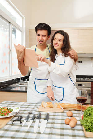 Positive young Caucasian couple in aprons reading recipe in cooking book when making dinner together Stok Fotoğraf