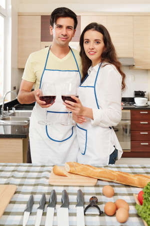 Young Caucasian couple in aprons standing at kitchen table with wine glasses in hands and looking at camera