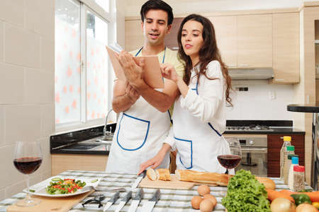Young Caucasian couple reading list of ingredients in cooking book when making new Fresh dish for dinner at home