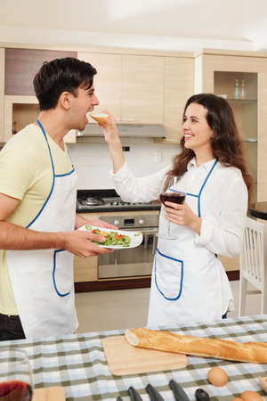 Positive young Caucasian couple eating salad with wine and French baguette in kitchen