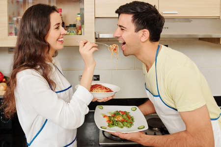 Happy young woman in love feeding her boyfriend with spaghetti when they are standing in kitchen after cooking dinner Stock Photo - 131721155