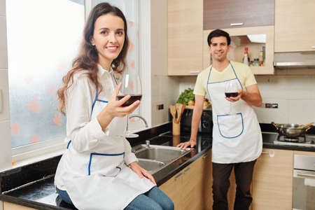 Young Caucasian couple in aprons enjoying red wine after cooking dinner at home