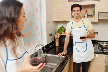 Portrait of handsome young smiling man in apron leaning on kitchen counter and drinking glass of red wine after washing dishes