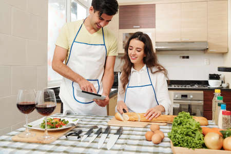 Smiling young man showing new recipe on tablet computer to his cooking wife