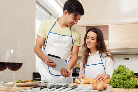 Smiling young Caucasian couple in aprons discussing new recipe on tablet computer when cooking in kitchen