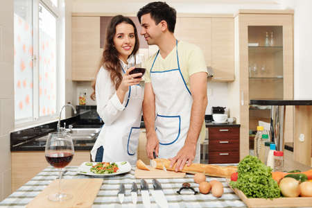 Handsome young man cutting French baguette and looking at his beautiful wife drinking glass of red wine