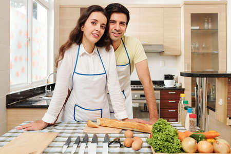 Portrait of young positive Caucasian couple standing at kitchen table with utensils and dish ingredients