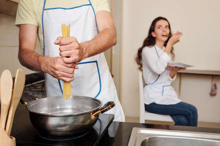 Young man putting spaghetti in boiling water when his wife eating salad in background