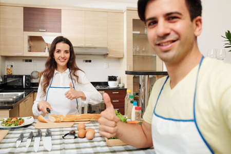 Positive young Caucasian husband and wife cooking dinner together in kitchen and showing thumbs-up Stok Fotoğraf