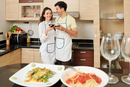 Cheerful young Caucasian couple in aprons toasting with glasses of red wine and celebrating small anniversary at home