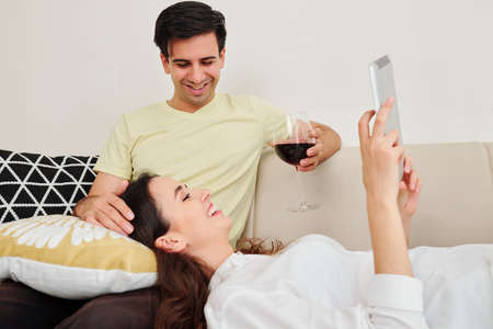 Happy handsome young man drinking glass of red wine and looking at his smiling wife watching movie of digital tablet