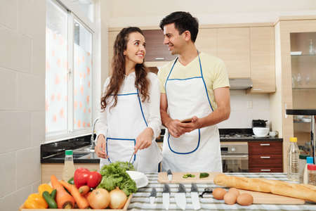 Happy young couple in love standing at kitchen table with fresh products and looking at each other