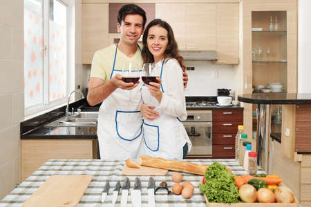 Young Caucasian couple in aprons drinking red wine when cooking dish of French cuisine at home