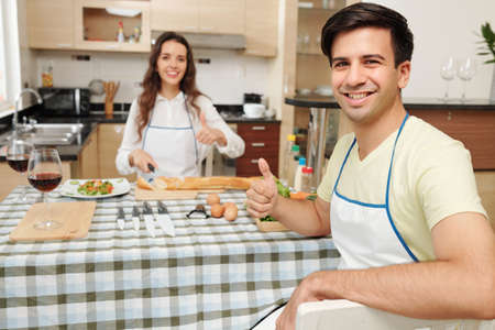 Happy young Caucasian couple cooking dinner in kitchen and showing thumbs-up
