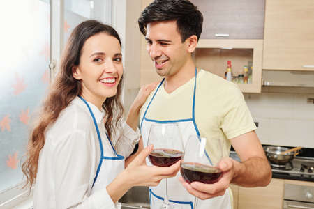 Smiling young man looking at his girlfriend and toasting with glass of red wine Stok Fotoğraf