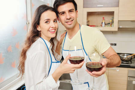 Portrait young smiling boyfriend and girlfriend standing in kitchen with wine glasses and looking at camera Stok Fotoğraf