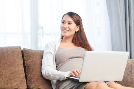 Smiling young pregnant Asian woman working on laptop when sitting on sofa at home