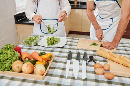 Couple cutting cucumbers and mixing lettuce leaves with dressing for delicious healthy salad for dinner