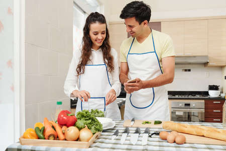 Cheerful young man showing funny pictures on smartphone screen to girlfriend who is mixing healthy salad for dinner Stok Fotoğraf