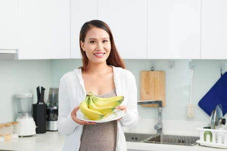 Smiling young Vietnamese pregnant woman standing in kitcha and showing bunch of fresh bananas Stok Fotoğraf