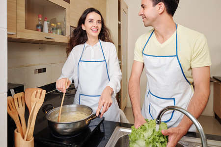 Beautiful happy young woman mixing spaghetti in boiling water when her husband rinsing vegetables for salad