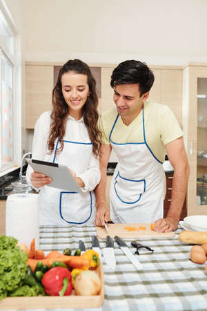 Positive young Caucasian couple checking soup recipe on digital tablet when cooking at home 版權商用圖片