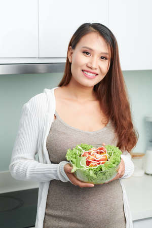 Smiling lovely young Vietnamese woman showing bowl of healthy salad she is going to have for lunch