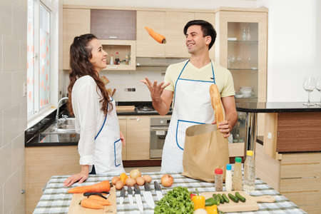Smiling handsome young man tossing carrots when taking vegetables out of grocery bag in front on his wife