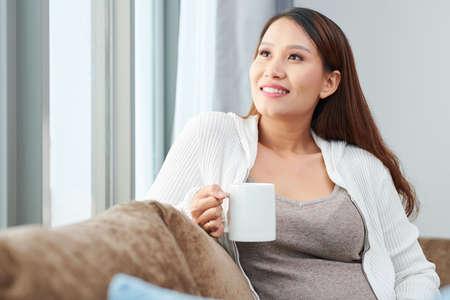 Portrait of smiling pensive pregnant young Asian woman enjoying big mug of delicious hot beverage