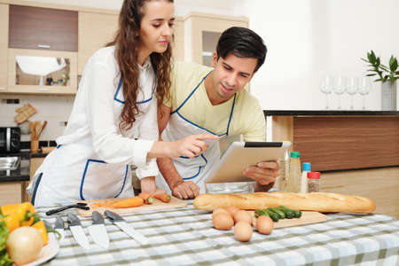 Young Caucasian couple in aprons reading recipe in tablet computer before cooking dinner together Stok Fotoğraf