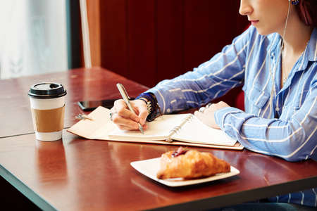 Cropped image of creative young woman sitting at table with coffee and croissant for breakfast and writing down her plans