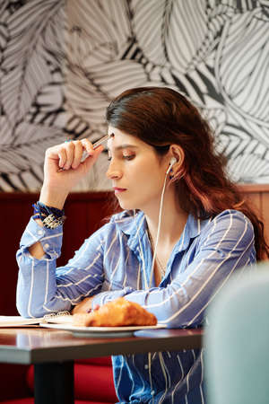 Young pensive female student sitting at cafe table, listening tin music and doing homework for tomorrow class Banco de Imagens