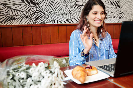 Smiling female teacher of English in earphones sitting in front of laptop in cafe and teaching online class Stock Photo