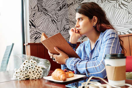Pensive young woman with opened book in hands sitting at cafe table with flowers bouquet, pastries and coffee and looking through window Reklamní fotografie - 129375209