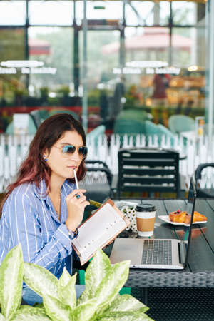 Pensive young businesswoman in sunglasses sitting at table in cafe and posndering over plans for the day Banco de Imagens