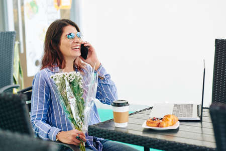 Happy young woman with flowers bouquet in hands talking on phone when having breakfast in cafe on her birthday Reklamní fotografie