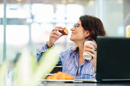 Happy young woman enjoying delicious pastry and cup of fresh coffee in local caffeteria