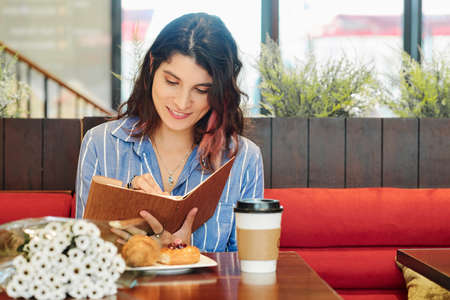 Pretty smiling young woman sitting at table in cafe with coffee and couquet of flowers and taking notes in diary