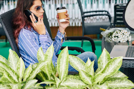 Beautiful young woman leaning back in chair, drinking cup of take away coffee and calling on phone