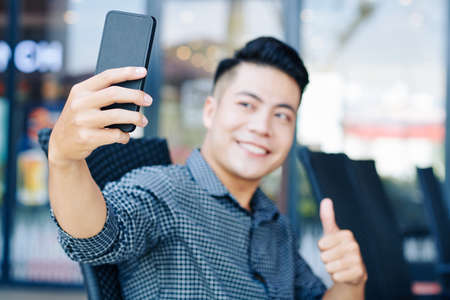 Handsome young Asian man showing thumbs-up when taking selfie on smartphone outdoors Banco de Imagens