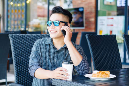 Positive young man sitting at table in cafe and smiling when talking to friend on the phone