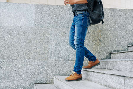 Cropped image of man in jeans with big backpack walking down the stairs and drinking cup of take away coffee