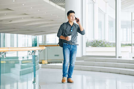 Young Asian man with backpack and coffee cup standing in hall of university building and making phone hall
