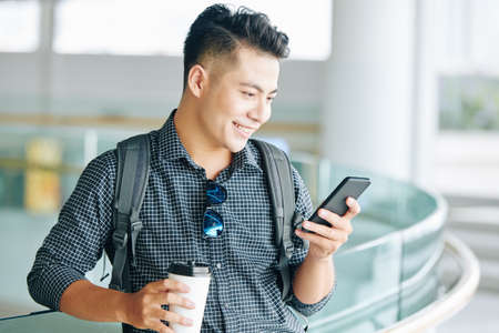 Positive young Asian man drinking take away coffee and reading text messages in his smartphone