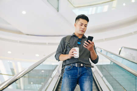 Serious Vietnamese university student standing on escalator with cup of coffee and reading messages on his phone