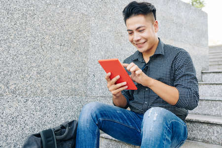 Portrait of young handsome Asian man resting outdoors and using application on table computer