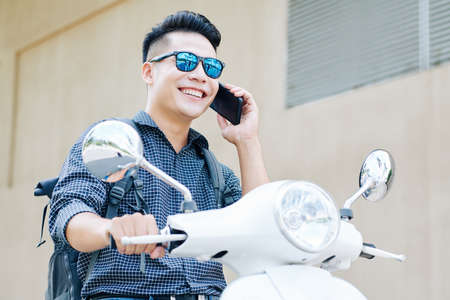 Cheerful young Vietnamese man riding on scooter in the city and talking on phone with friend