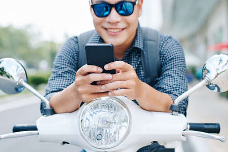 Happy young Asian man in sunglasses sitting on scooter and checking text messages and notifications in his phone, selectie focus Banco de Imagens