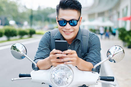 Positive young Vietnamese man sitting on his scooter and playing addictive game on smartphone